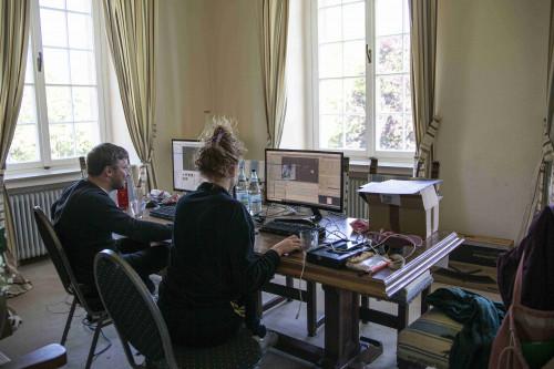Fabian Raith und Natalie Sontopski von den Code Girls sitzen in der Burg Hülshoff an einem großen Holztisch mit Bildschirmen, Tastauren und vielen Kabeln.mit