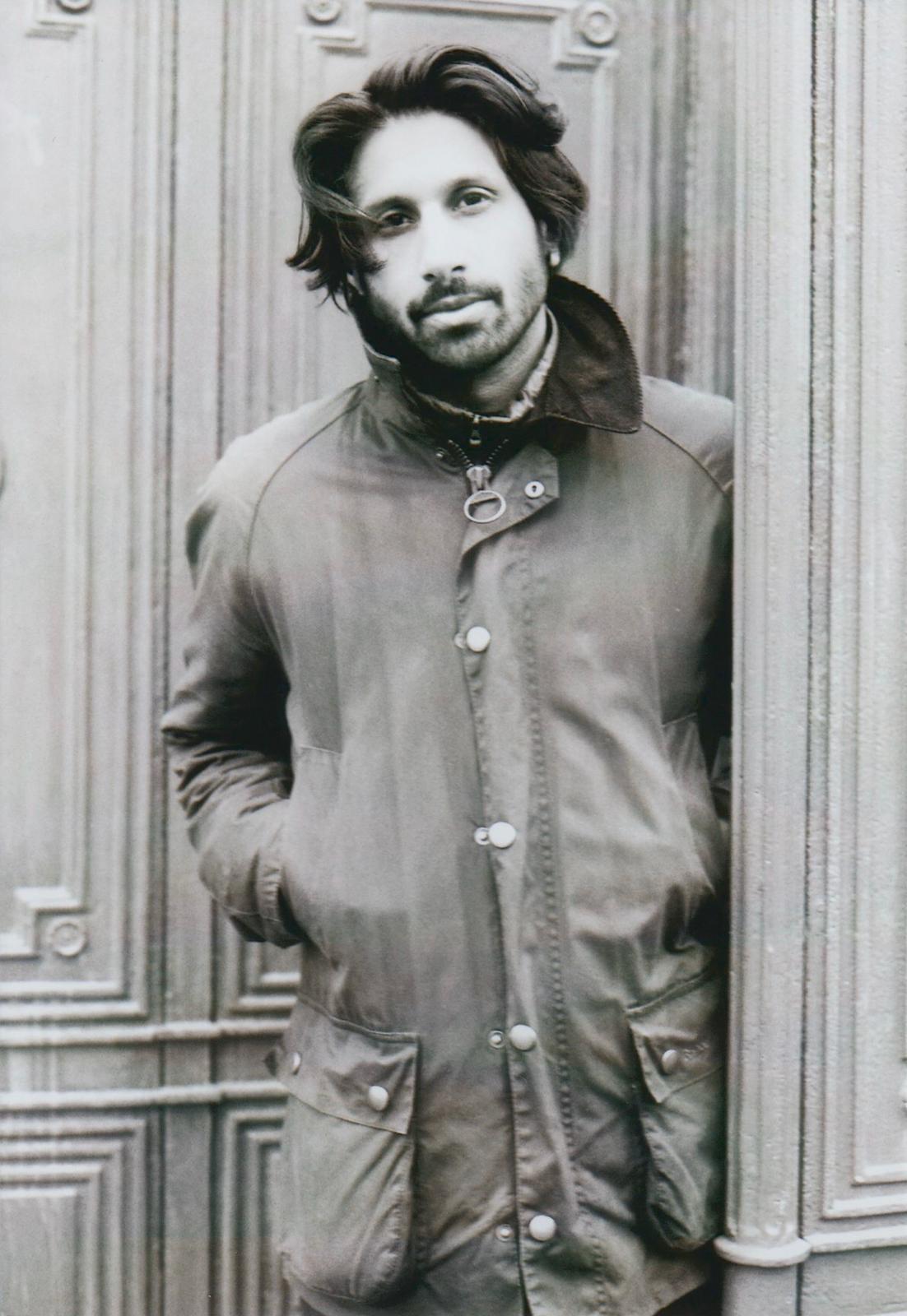Ein schwarz-weiß Foto von Ralph Tharayil, der mit den Händen in der Jackentasche in einer Tür steht und in die Kamera blickt.