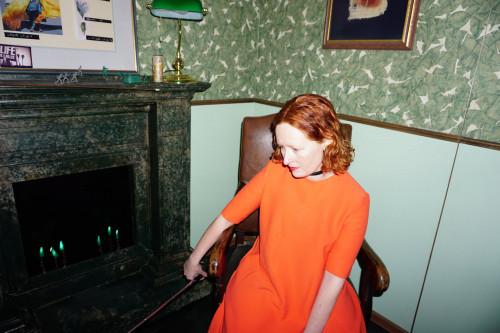 Nadine Finsterbusch sitzt mit rotem Haar und orangenem Kleid in einem Lederstuhl vor einem Kamin und einer Tapete mit grünen Blättern. Sie schaut nach unten links und wird vom Blitz erleuchtet.