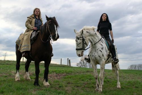 Karen Duve und Bettina Bruns sitzen auf Pferden auf einer grünen Wiesen Landschaft.