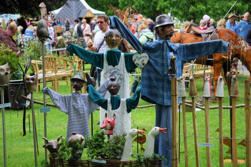 Handgefertigte Puppen stehen auf einer grünen Fläche, im Hintergrund sieht mensch die Besucher*innen der Gartenträume 2019.